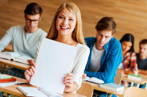 最高になりました。白い紙を持って、教室のフロントに座ってカメラを見ている陽気な若い女性