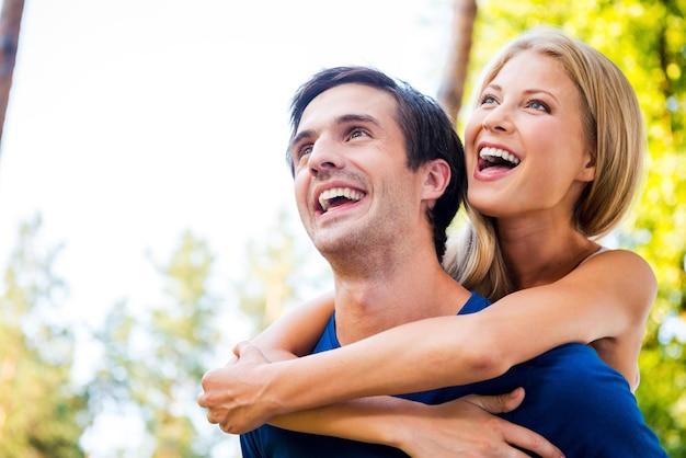 함께해서 행복합니다. 여자가 뒤에서 남자친구를 껴안고 웃고 있는 동안 야외에서 함께 서 있는 행복한 젊은 부부의 낮은 각도 보기