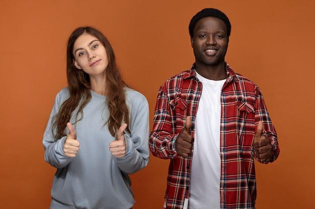 一緒にいて幸せです。ポジティブで陽気な若いアフロアメリカ人の男と彼のかわいい長い髪の白人のガールフレンドが一緒に時間を楽しんで、楽しく笑って、親指を立てるジェスチャーを見せている写真