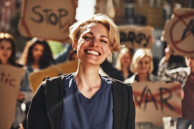 私の権利のために戦う幸せ幸せな若いブロンドの女性に愛という言葉が書かれています