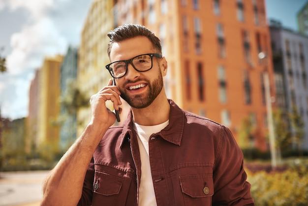 カジュアルな服装と眼鏡をかけた明るくハンサムなひげを生やした男の肖像画が電話で話し、通りに立って笑っています。ポジティブな感情。デジタル。コミュニケーション