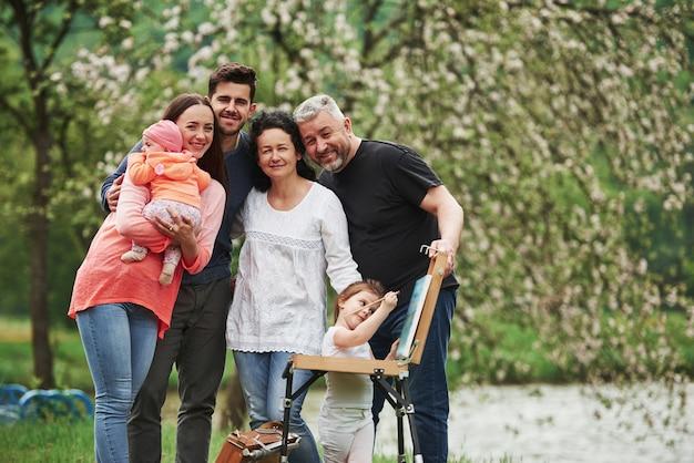 お互いに会えてうれしい。家族は公園で楽しい時間を過ごします。描く方法を教える若い画家