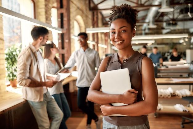 Счастлива работать здесь молодая и веселая афроамериканская женщина, держащая ноутбук и улыбающаяся стоя