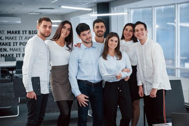 一緒に働いて幸せ。現代の良い明るいオフィスでクラシックな服を着た若いチームの肖像画