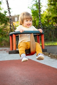 Happy toddler, baby or child on playground area. playingat swing. education, parenting, active games outside.