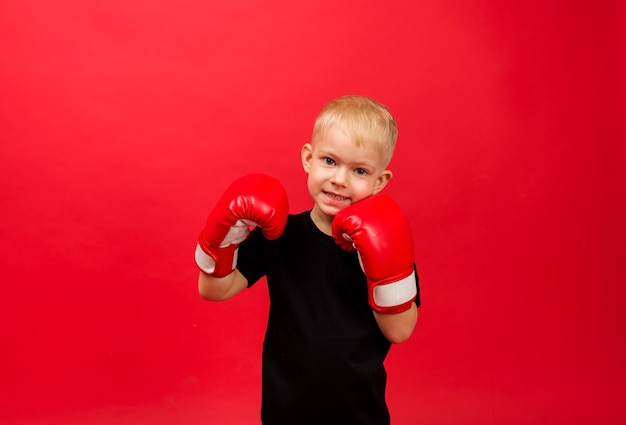 Happy toddler boy boxer in red boxing gloves on red wall