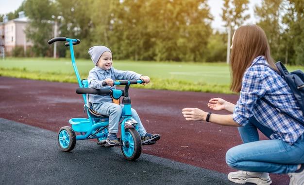 행복한 유아 소년이 성공적으로 어린이 세발 자전거를 타고 어머니에게 가고 있습니다.