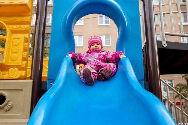 추운 날씨에 놀이터에서 미끄럼틀에서 노는 행복한 어린 소년