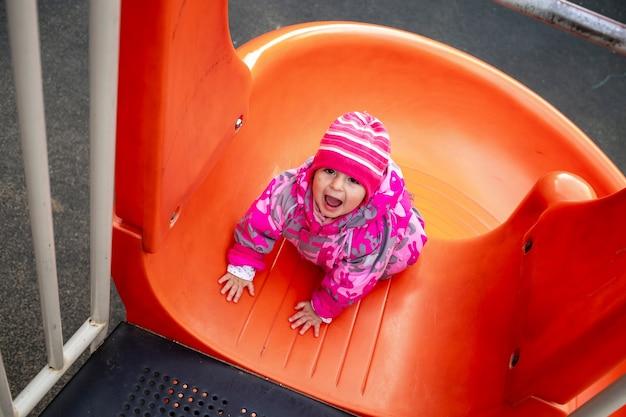 놀이터에서 미끄럼틀에서 노는 행복한 유아 소년