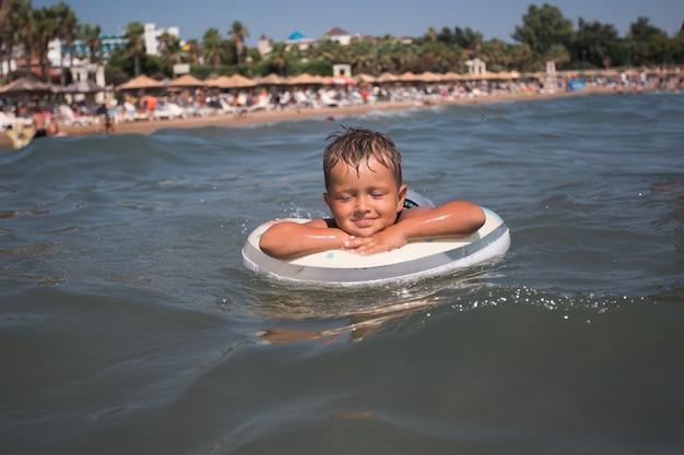 海で泳ぐ幸せな幼児の男の子