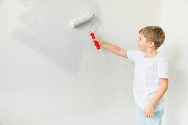 행복 한 유아 어린이 그림 벽. 아파트 수리. 새 아파트로 이사하는 개념. 방에 귀여운 작은 소년 그림 벽