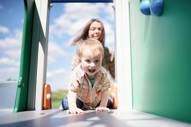 Happy toddler climbs on the slide on the playground