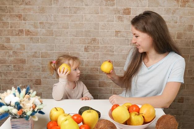 幸せな幼児の女の子と彼女の美しい若い母親は、朝食を作り、自宅のキッチンで一緒に新鮮な果物を食べます