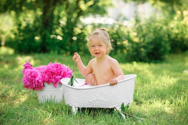 幸せな幼児の女の子は、花びらが付いているミルクバスを取ります。ミルクバスの少女。ピンクの牡丹の花束。赤ちゃんの入浴。幼児の衛生とケア。