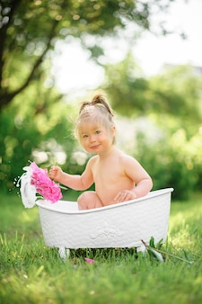 Счастливая девушка малыша принимает молочную ванну с лепестками. маленькая девочка в ванне молока на зеленом цвете. букеты из розовых пионов. детское купание.