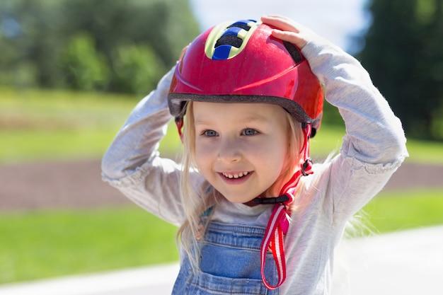 Счастливая девушка малыша нося красный пластичный шлем outdoors. портрет симпатичной 4-летней девочки, держащей шлем на голове руками