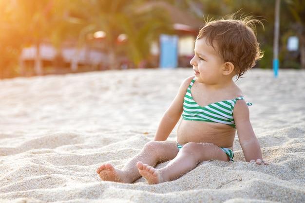 Счастливый малыш в купальнике сидит на песчаном пляже в лучах солнца.