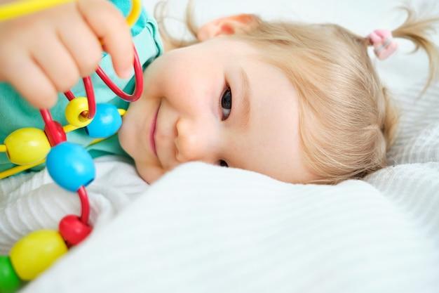 幸せな幼児はベッドサイドのおもちゃで遊ぶ