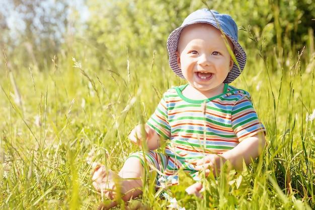 幸せな幼児は晴れた夏の日に草の上に座っています