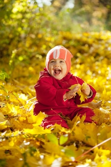 Happy toddler sitting on maple leaves