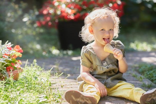 Счастливый малыш с мороженым сидит на траве в лучах солнца
