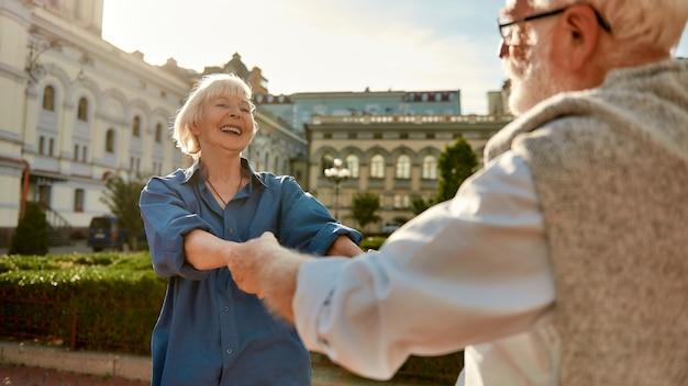 야외에서 춤을 추고 웃고 있는 아름다운 노부부가 함께 행복하다