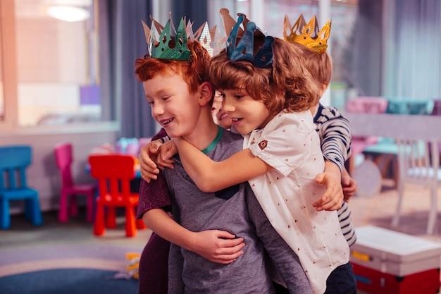 一緒に幸せ。彼の友人を抱きしめながら彼の顔に笑顔を保つ陽気なブルネットの少年