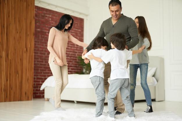 Счастливы вместе, полный снимок красивой латинской семьи, развлекающейся в помещении, мама и папа