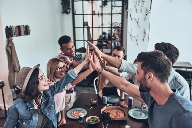 一緒に幸せ!夕食会をしながら、団結と笑顔を象徴するハイタッチをする若者たちの平面図