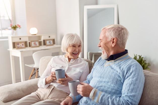 一緒に幸せ。陽気な年配のカップルがリビングルームのソファに座って、コーヒーを飲みながら、お互いに笑顔でおしゃべり