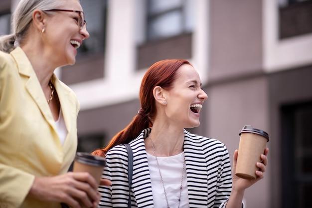一緒に幸せ。紙コップが屋外で笑い、遠くを見ている2人の満足しているビジネス女性のウエストアップ