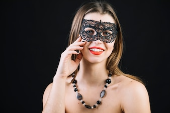 Happy topless woman wearing masquerade carnival mask over black background