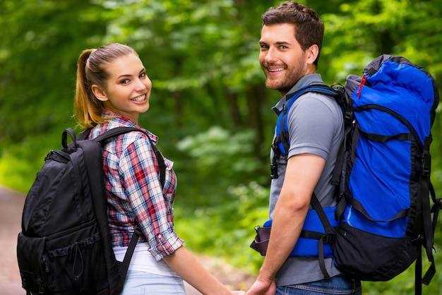 Happy tourist couple. beautiful young loving couple carrying backpacks and looking over shoulder with smile while walking along the forest pathway