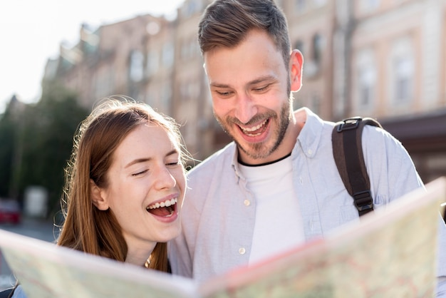 Happy tourist couple looking at map