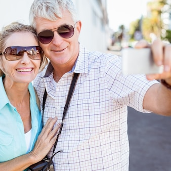 Happy tourist couple taking a selfie in the city
