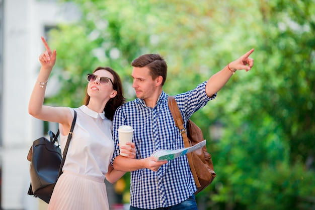 Happy tourist couple traveling in europe smiling happy. caucasian friends with city map in search of attractions. young man with hot coffee and beautiful woman with big map