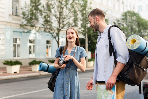 Happy tourist couple with camera and backpacks