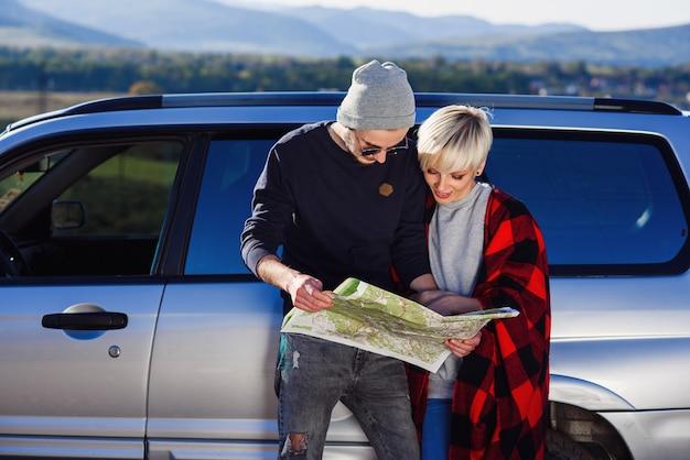 レンタカーの近くの紙の地図と幸せな観光カップル。
