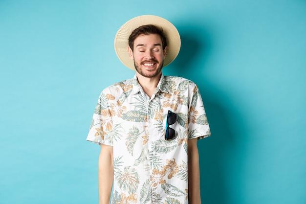 麦わら帽子とアロハシャツを着て、青い背景の上にうれしそうに立って、夏休みを楽しんでいる幸せな観光客。