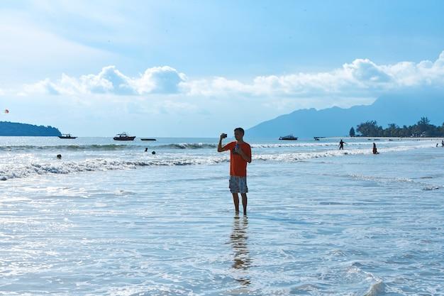 Счастливый туристический парень на центральном пляже тропического острова лангкави