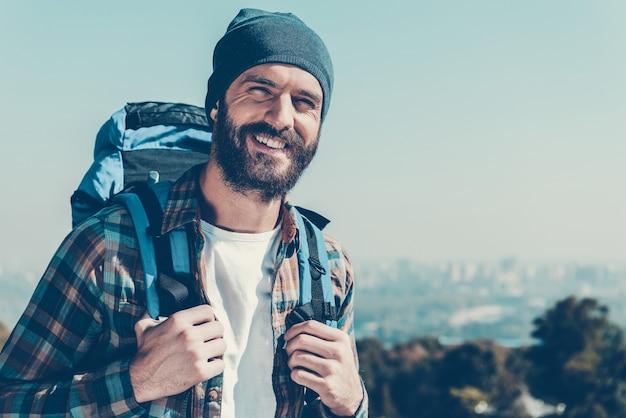 幸せな観光客。バックパックを背負って、自然の中で立っている間笑顔でカメラを見てハンサムな若い男