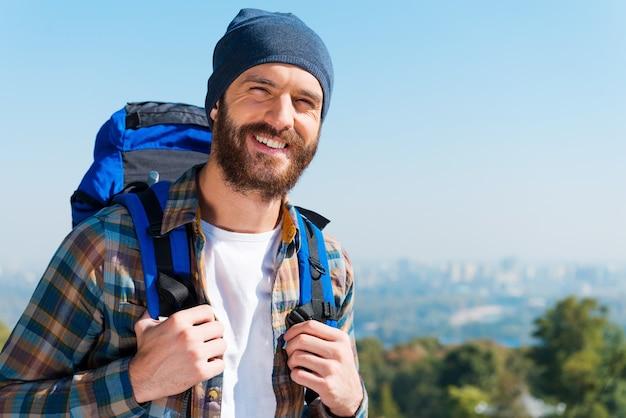Счастливый турист. красивый молодой человек, несущий рюкзак и смотрящий в камеру с улыбкой, стоя на природе