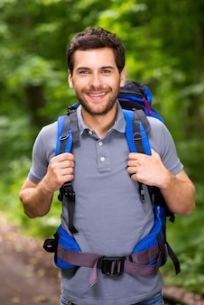 Happy tourist. handsome young man carrying backpack and looking at camera with smile while standing in the nature