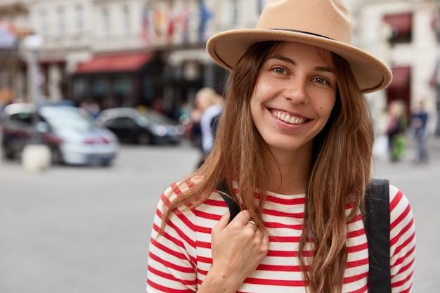 Il turista felice ha un'espressione felice, indossa un copricapo alla moda