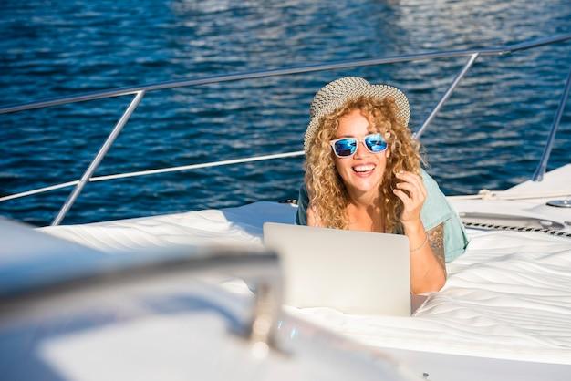 幸せな観光客は、旅行クルーズ活動でボートに横になっている夏休みの休暇で太陽を楽しんでいます-女性の人々は笑顔でローミング接続のラップトップコンピューターを使用しています