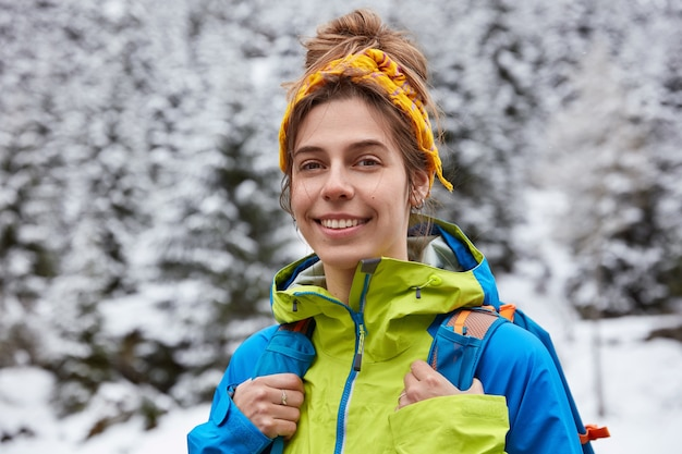 Happy tourist poses on snowy mountain top, enjoys winter day trekking, wears yellow headband, casual jacket