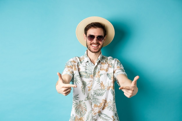 Happy tourist in summer hat and hawaiian shirt, pointing fingers at logo on center, showing something, standing on blue background.