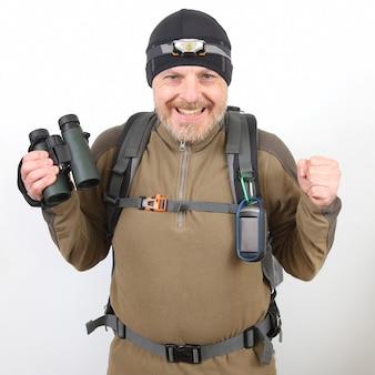 Счастливый туристический путешественник с биноклем в руке на белом