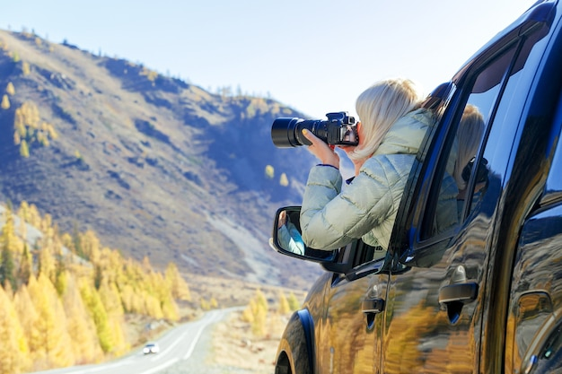 Happy tourist travelling in countryside. tourist woman in an open window of a auto car taking photography. blogger using hobby content concept, enjoy trip.