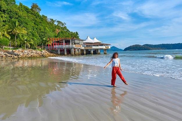 幸せな観光客の女性は、ランカウイ熱帯の島の中央のビーチで旅行をお楽しみください